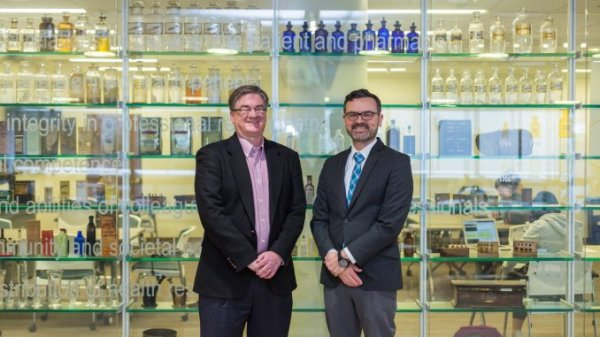 Two college faculty leaders standing in front of glass window with bottles displayed. of