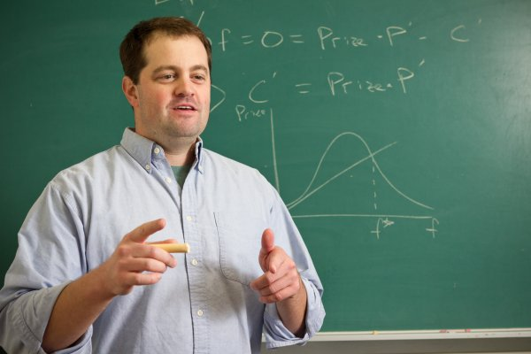 Todd McFall, Assistant Teaching Professor of Economics posses for photo in front of chalkboard.
